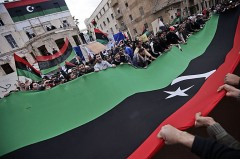 crowds in Benghazi holding a giant libyan flag