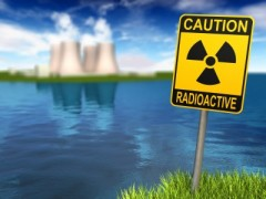 Warning sign with radioactive symbol and nuclear power plant on the coast